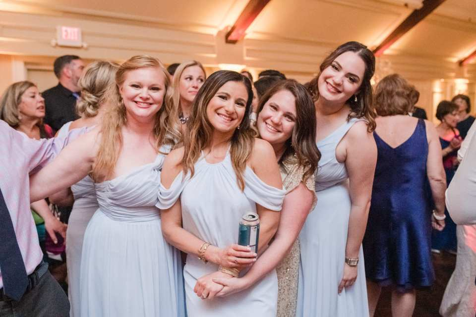 fun photo of members of the bridal party in light blue Watters gowns, along with other guests, smiling during the wedding reception