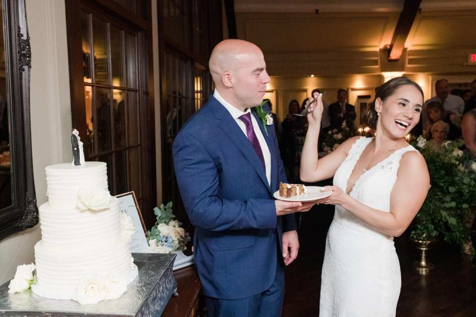 Bride in Pronovias laughs as she feeds her groom a bit of their three tier white wedding cake by Sweet Spot Bake Shoppe during the cake cutting. Groom in navy blue Jos. A. Banks