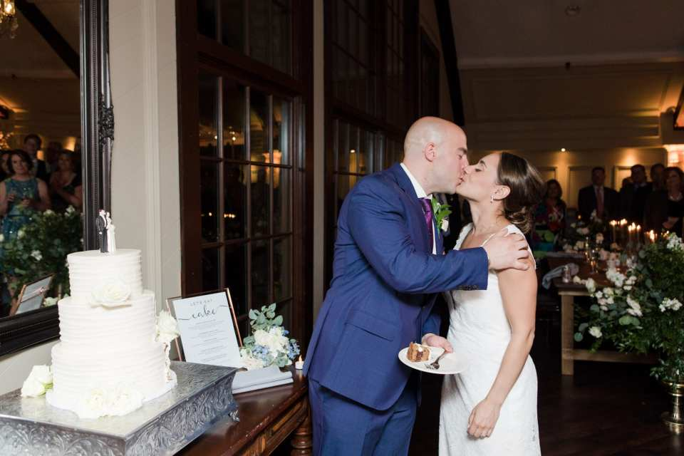 Bride and groom kiss after taking part in the cake cutting, three tier white wedding cake by Sweet Spot Bake Shoppe