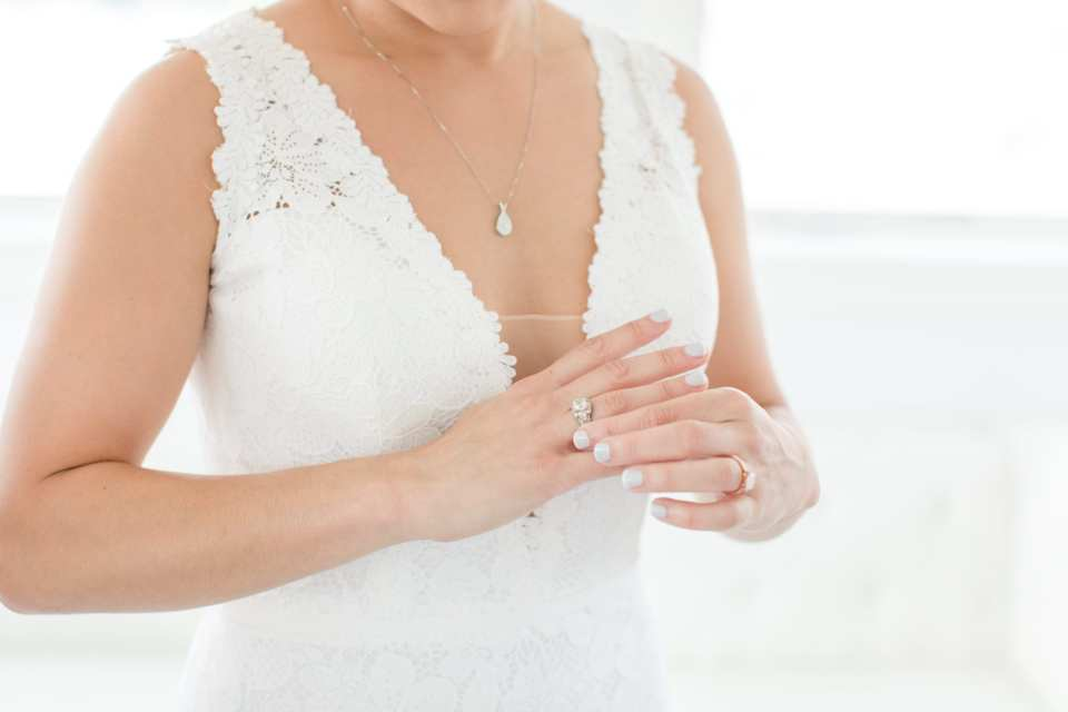 zoom in on the details of the bride putting on her rings, lace gown by Pronovias
