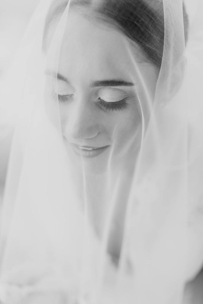Black and white photo of brides face under her veil