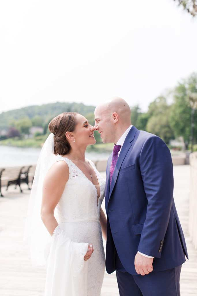 Bride in v-neck lace gown by Pronovias, groom in navy blue suit by Jos. A. Banks, on the boardwalk outside the Lake Mohawk Country Club