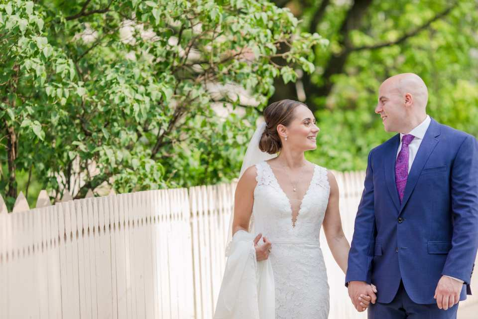 Bride in v-neck lace gown by Pronovias, groom in navy blue suit by Jos. A. Banks, walk outdoors, hand in hand