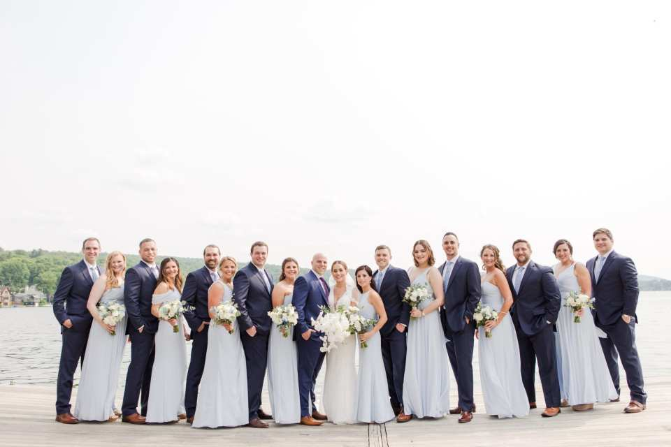 formal wedding party photo outdoors on the dock at the Lake Mohawk Country Club. Men in navy blue Jos. A. Banks suits, women in light blue gowns by Watters. Bride in Pronovias. Florals by From Peonies to Paint Chips