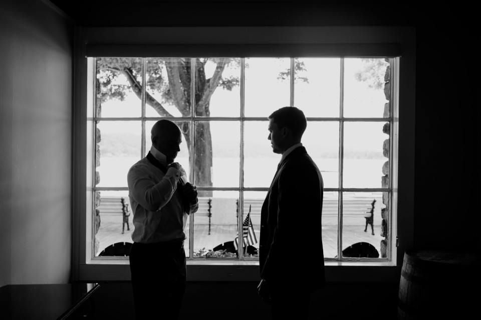 black and white photo of the groom getting ready with a groomsman looking on, set in front of a large window