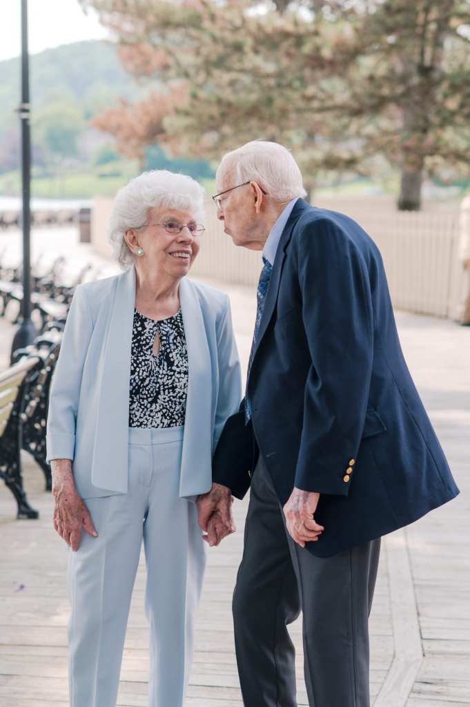 an older couple, woman in light blue pants suit, man in navy blue pant suit, outside the event space, looking lovingly at each other while holding hands.