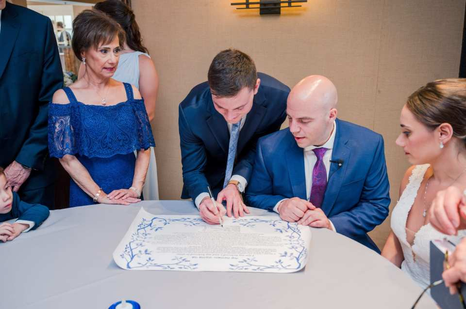 Parents of the bride, groom, surrounded by friends and family take part in the signing of the Ketubah
