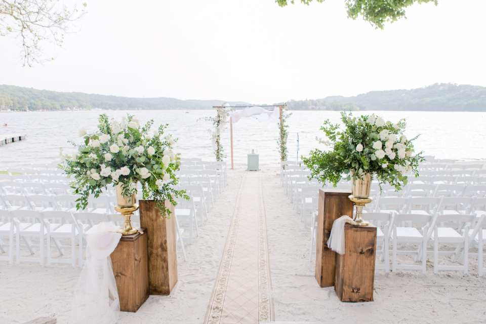 wide angle photo of the wooden chuppah covered with traditional prayer shawl and creeping greens in front of the lake at the Lake Mohawk Country Club