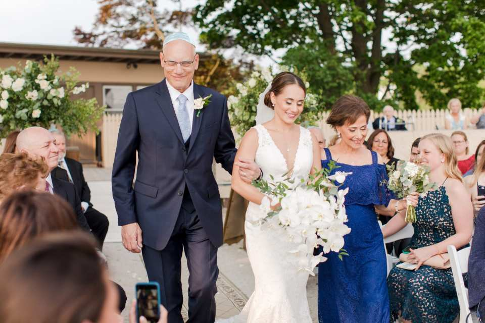 bride in deep vneck lace gown by Pronovias, carrying a cascading bouquet of white orchids by From Peonies to Paint Chips, being walked down the aisle by her mother and father.