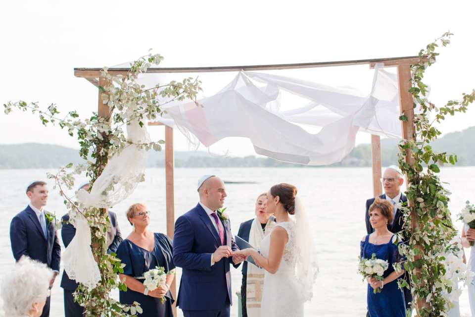 the bride and groom exchange rings under a traditional chuppah, covered in traditional prayer shawl, with greens climbing the wood of the chuppah, against the lbackdrop of the lake at Lake Mohawk Country Club