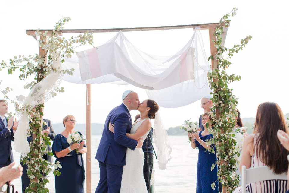 the bride and groom kiss as husband and wife under a traditional chuppah, covered in traditional prayer shawl, with greens climbing the wood of the chuppah, against the lbackdrop of the lake at Lake Mohawk Country Club