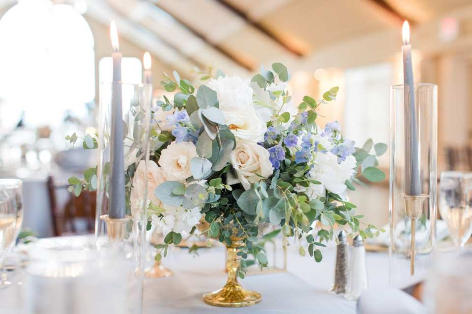 close up of a From Peonies to Paint chips low floral table arrangement of greens, cream and tiny blue florals with tall blue taper candles on either side