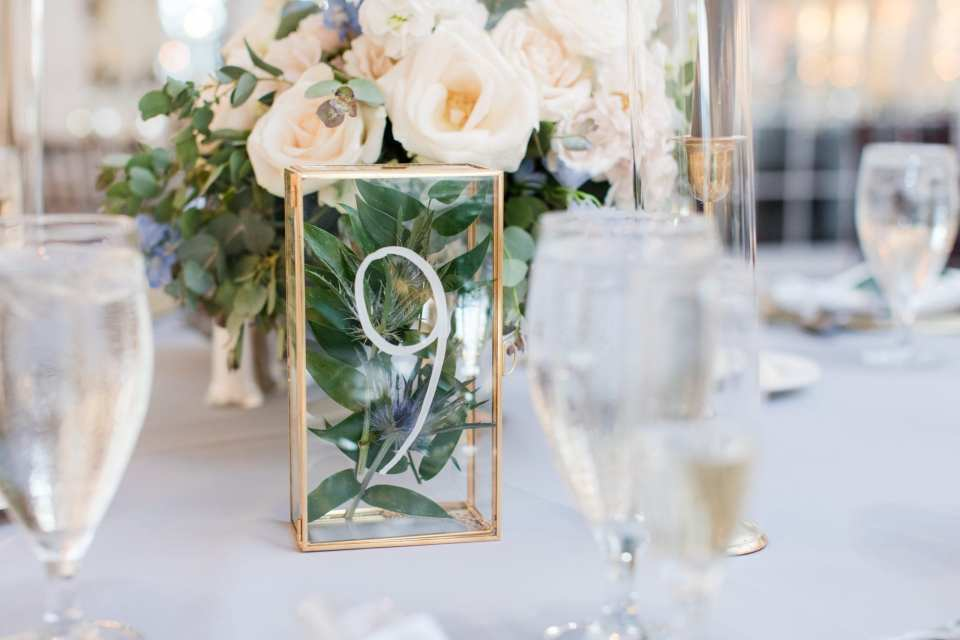 close up photo of a rectangular glass and gold framed vase with greenery and cream roses inside with table number on it by From Peonies to Paint Chips