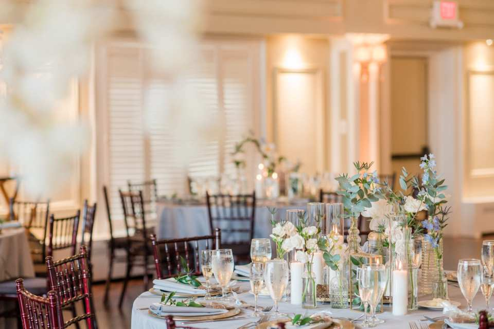 Focus on low white and blue floral arrangements, surrounded by candles and antique glassware by From Peonies to Paintchips in the ballroom for the wedding reception