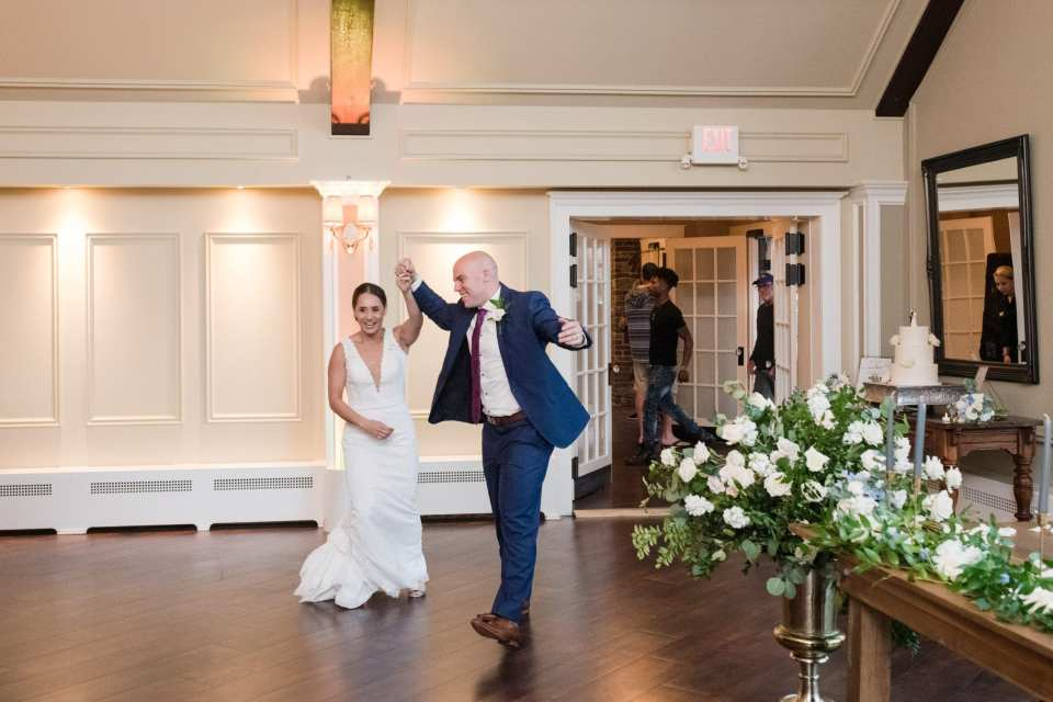 Bride in Pronovias gown, groom in navy blue Jos A Banks suit making their entrance as husband and wife into the ballroom, florals by From Peonies to Paint Chips