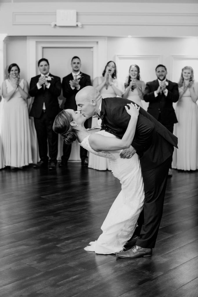 black and white photo of groom dipping his bride with a kiss during their first dance; wedding party in background