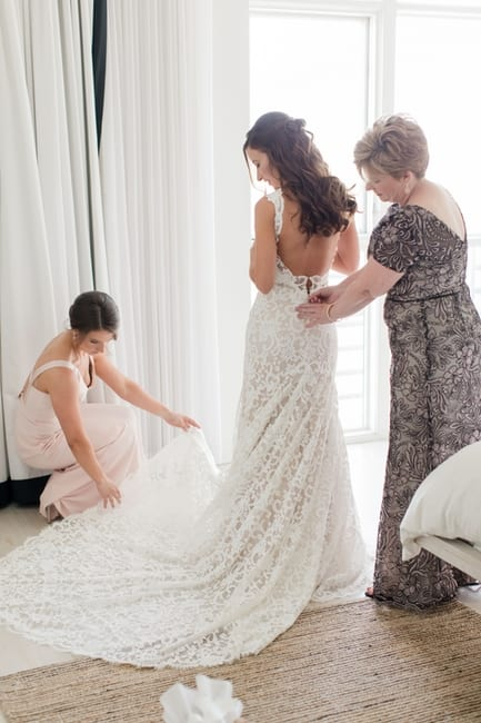 back full length view of the bride being buttoned into her gown by her mother while her maid of honor fixes the train on her gown in the bridal suite