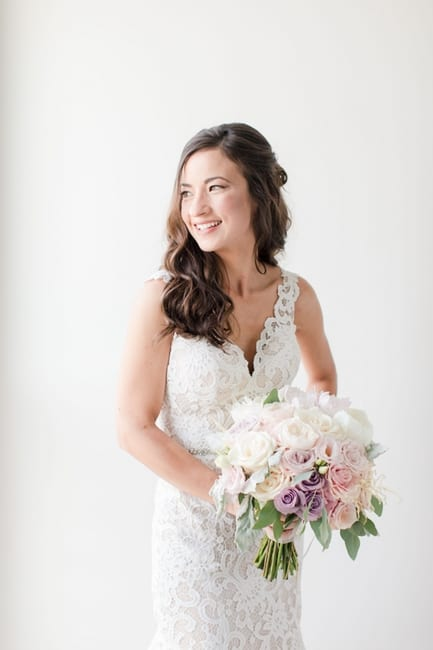 portrait of the bride in her lace gown, holding her bridal bouquet of white, blush, pink and lavender florals in the bridal suite