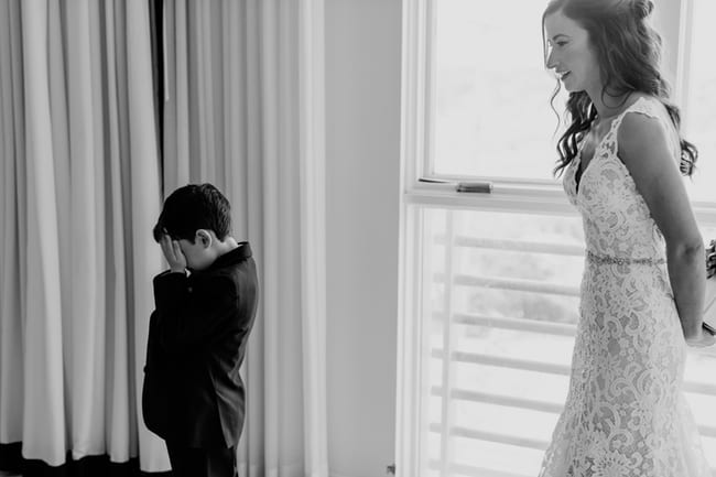 black and white photo of the bride about to surprise her soon to be stepson, his back to her, hands over his face