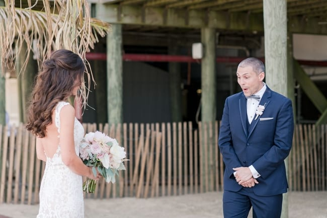 capturing the grooms look of shock and awe as he sees his bride for the first time under the boardwalk on the beach during their first look