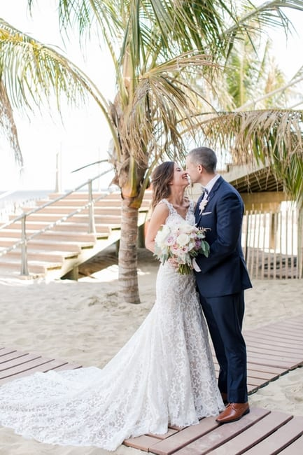 full length photo of the bride and groom on the beach for the first look, giggling at one another, palm tree in background