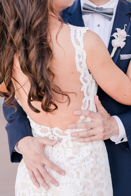 close up of the bottom 3/4 shot of bride and groom looking at each other focusing on the back of her lace gown outside on the boardwalk