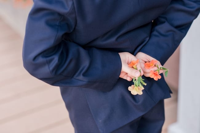 """close up of orange flowers the grooms son picked from a nearby plant that hes holding behind his back to """"surprise"""" his new stepmom with"""