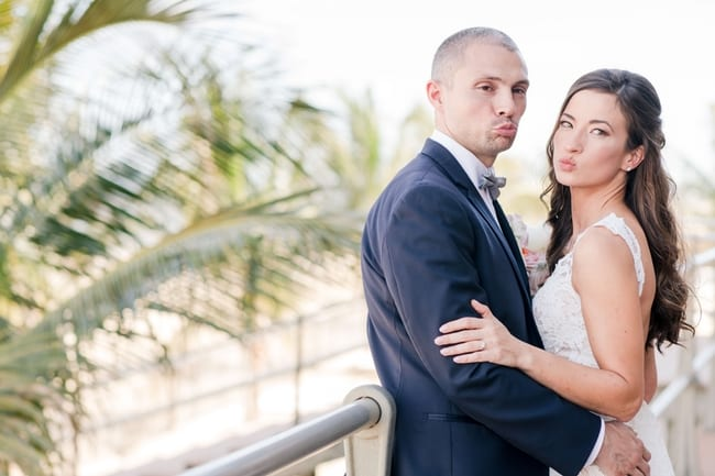 groom holding is bride while leaning against a rail outside in front of a palm tree making silly faces at the camera