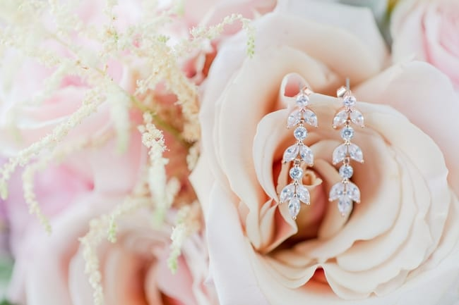 brides drop earrings perched on a cream colored rose in her bouquet