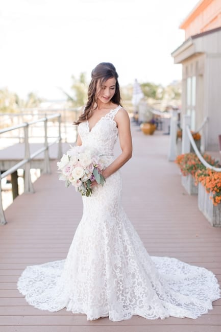 formal bridal portrait outside on the boardwalk with brides entire gown and train completely flowing out and she is holding her bouquet