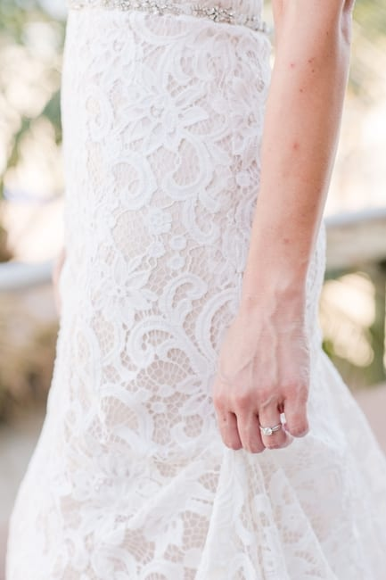 close up of the brides round engagement ring while holding a piece of her lace gown