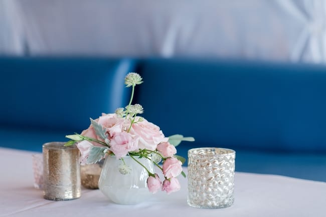 decor details from the space of various votives and small pink floral display
