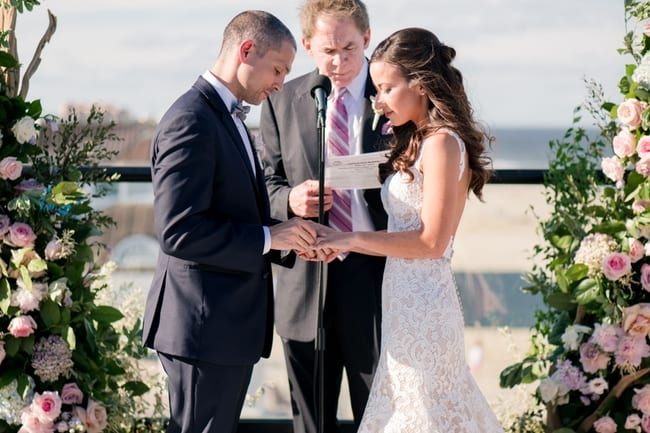 the bride and groom exchange rings overlooking the beach in front of custom floral altar pieces