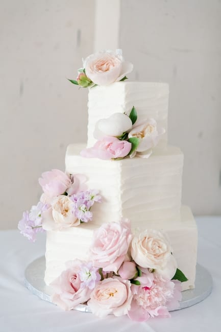 three tier polygon shaped cake with white frosting and lavender, pink, blush and white flowers
