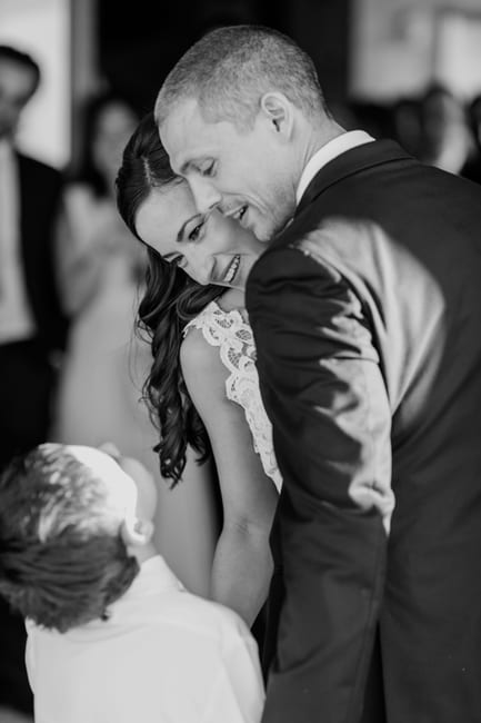 black and white photo of the bride and groom during their first dance, including the grooms son in the dance