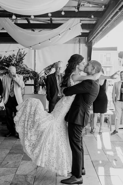 black and white photo of groom lifting bride and kissing her after first dance as husband and wife