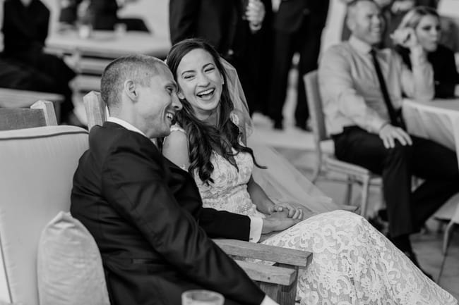 A black and white candid photo of the bride and groom holding hands and laughing during the toasts and speeches