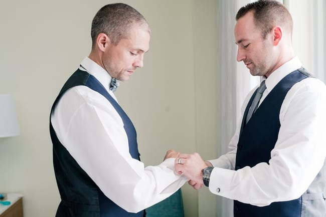 groom getting ready with assistance from his best man with the cuff links of his tuxedo