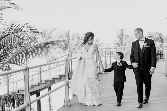 Black and white photo of the bride and groom strolling down the boardwalk with the grooms son in between them