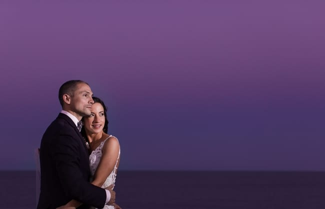 Bride wrapped in her grooms arms against a purple sunset sky