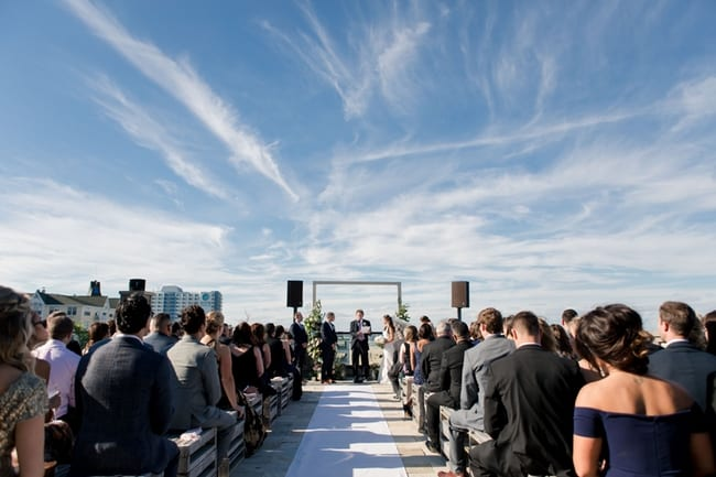 A wide shot of the bride and groom taking their marriage vows under a gorgeous bright blue sky with a few stray clouds