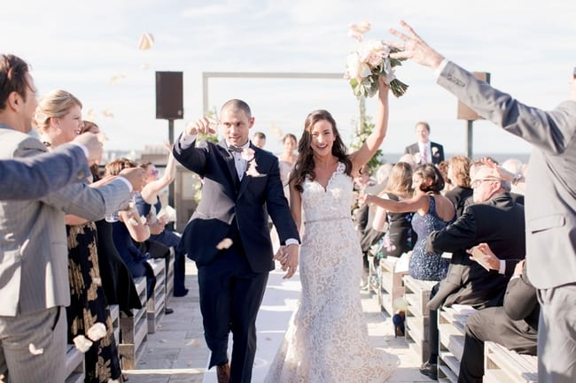the new mr and mrs walk down the aisle together under showers of rose petals