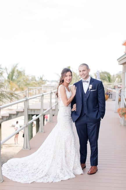formal full length portrait of the bride and groom on the boardwalk, with the brides entire lace gown extended while she has her arm through her grooms arm, her other arm on his shoulder