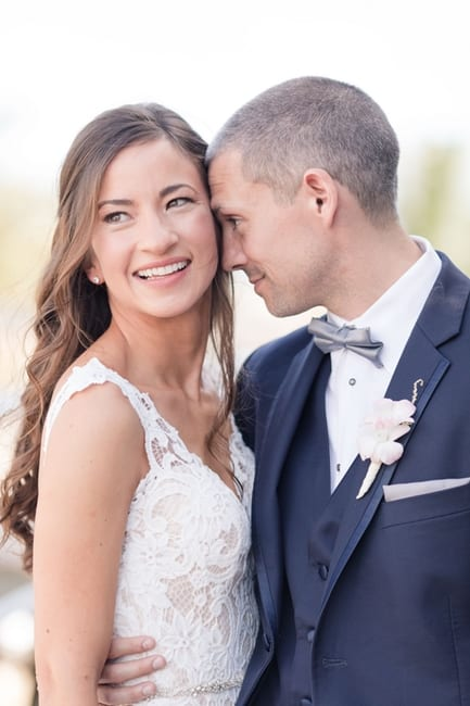 Portrait of bride and groom; bride looking off in the distance towards the camera, while the groom has his forehead to the side of her face
