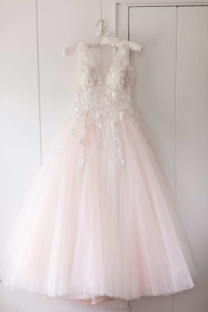 brides pink tulle jovani gown with petal details on the bodice hanging on a white padded hanger against a white paneled wall