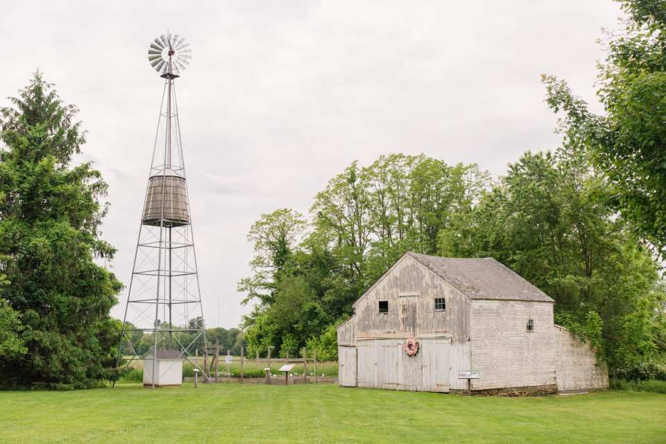 wide angle photo of the barn where the ceremony will be held with the windmill next to it on the Updike Farmstead property