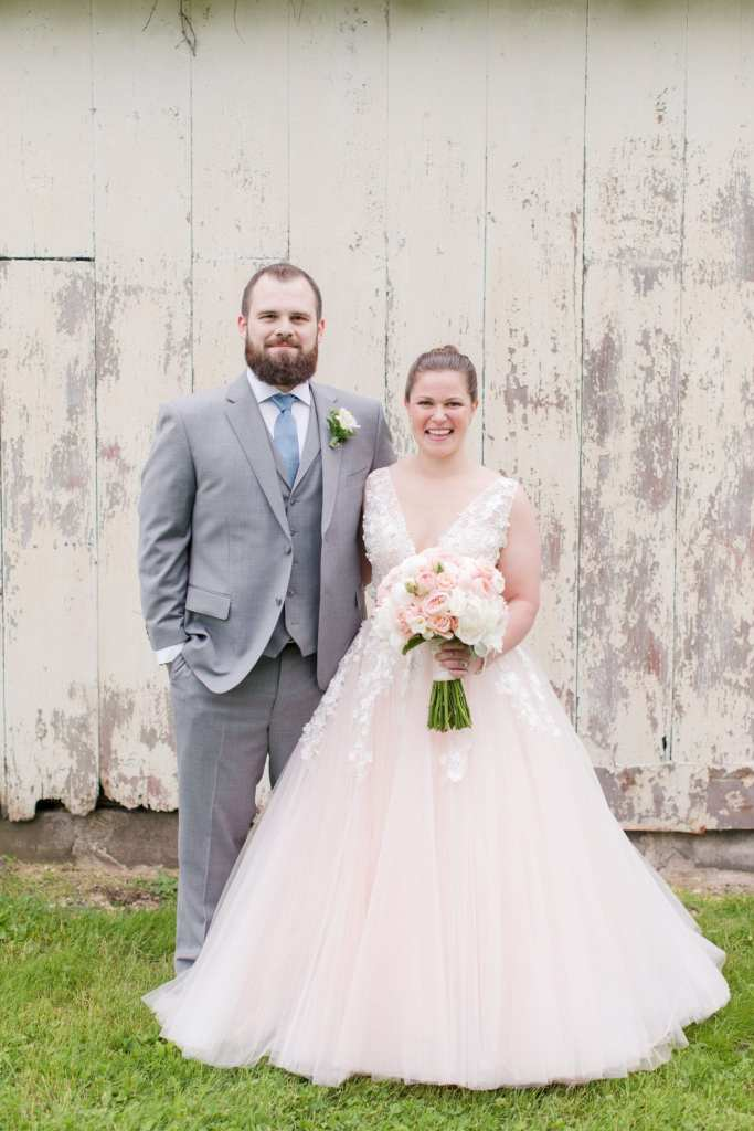 bride and groom side by side, each with an arm around the others waist, smiling towards the camera, during the first look outside of a white washed barn