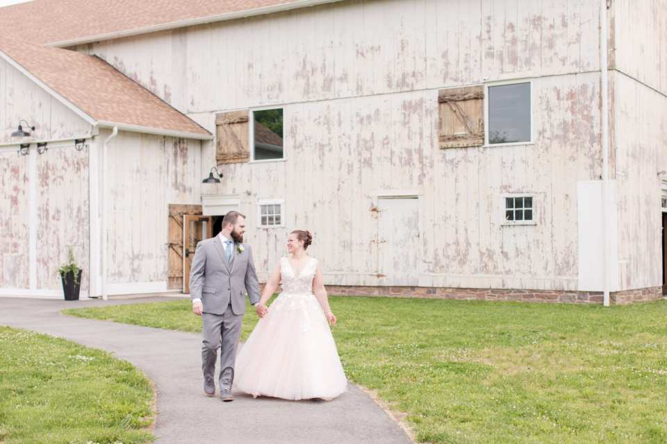 wide angle photo of the bride and groom walking hand in hand, while smiling at each other, along a path at the Updike Farmstead