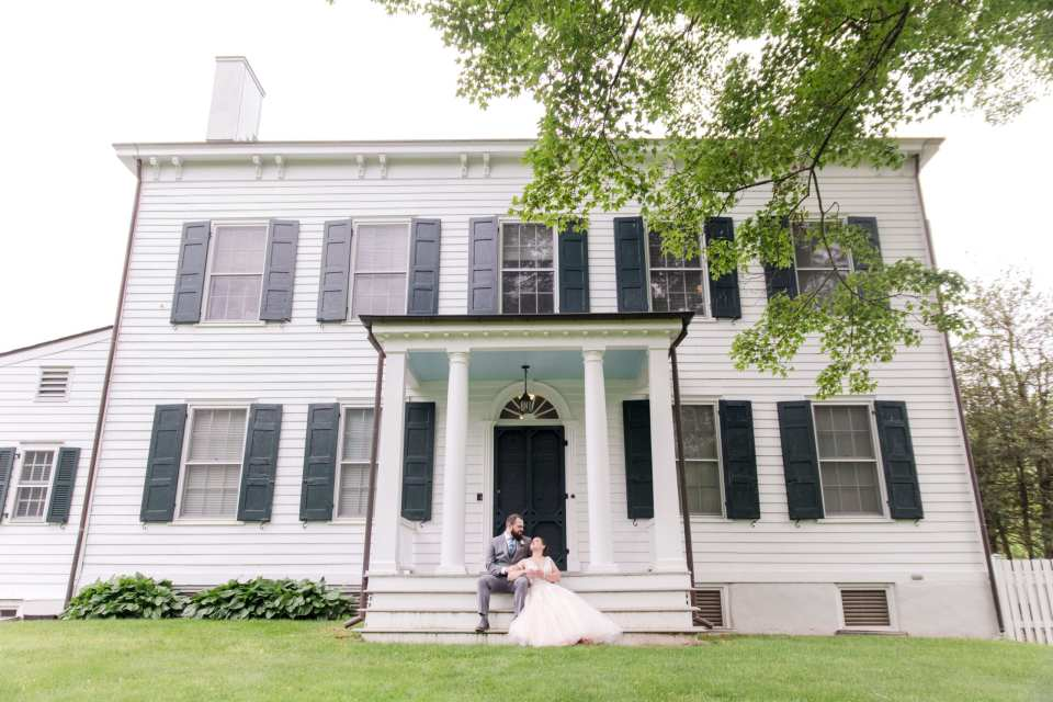 wide angle photo of the farmhouse at the Updike Farmstead, where the bride and groom are looking at one another while sitting on the front porch steps