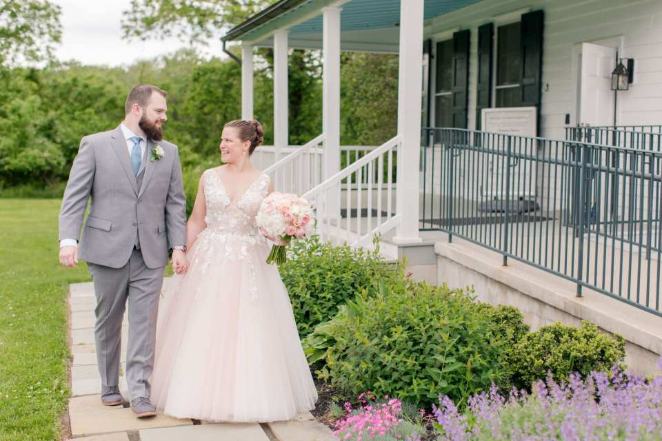bride and groom gazing at each other while walking hand in hand in front of the porch of the main house at the Updike Farmstead